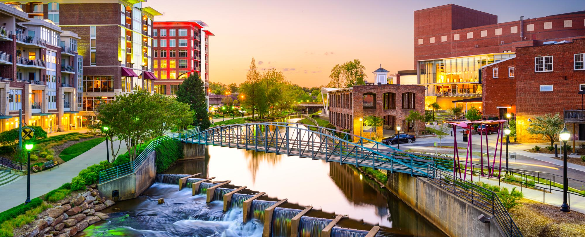 Downtown Greenville with a bridge and water underneath it