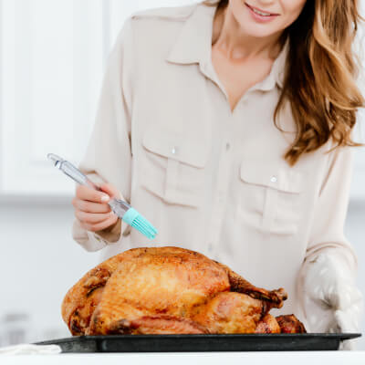 Woman basting turkey