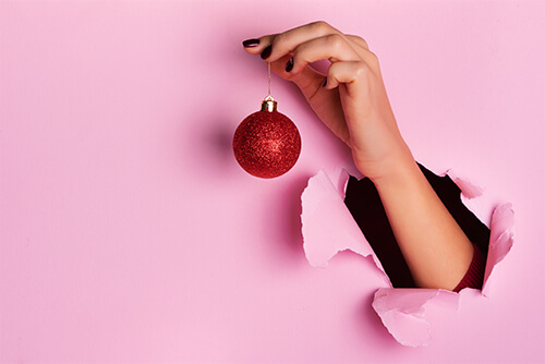 Hand reaching through a hole in pink construction paper. The hand is holding a red Christmas ornament