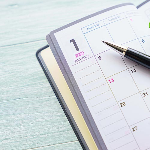 Monthly calendar planner with a pen resting on it on a background of white wooden boards